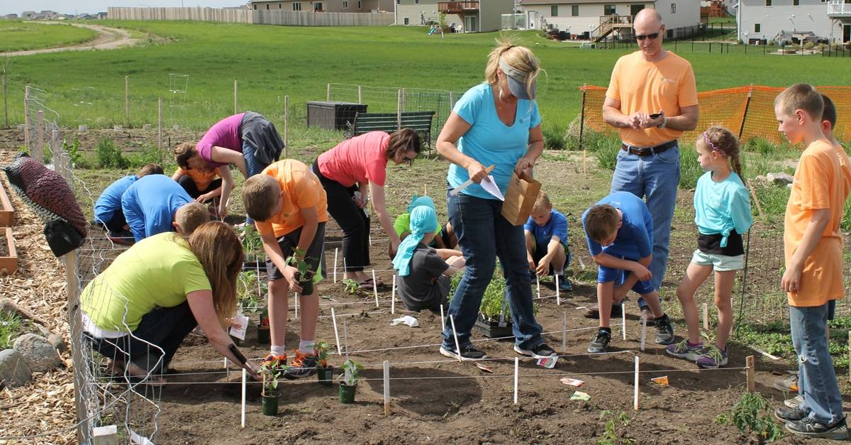 Kari Warberg Block, CEO of EarthKind Plants a Community Garden