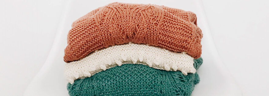 a stack of folded sweaters